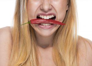 Frau mit Chili im Mund