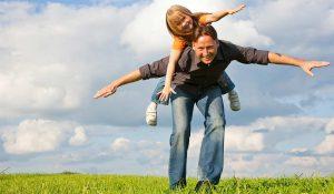 Mann balanciert Kind auf dem Rücken